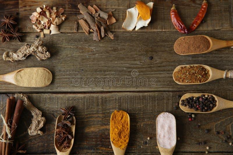 Kryddasortiment: gurkmeja ingefäran, kanel, muskotnöt, peppar, rosa färg saltar, stjärnaanis i träskedar på en träbakgrund royaltyfria bilder