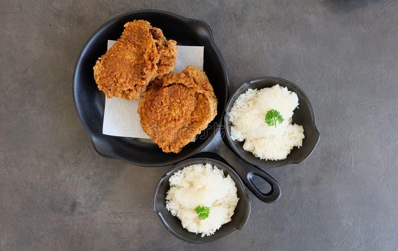 Kryddig frasig stekt kycklingportion med klibbiga ris p? den m?rka yttersidatabellen arkivbild