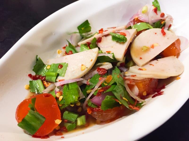 Kryddig och sur thailändsk klädd sallad med rimmad äggula, den vita grisköttkorven och grönsaker liksom vårlöken, persilja som to royaltyfri bild