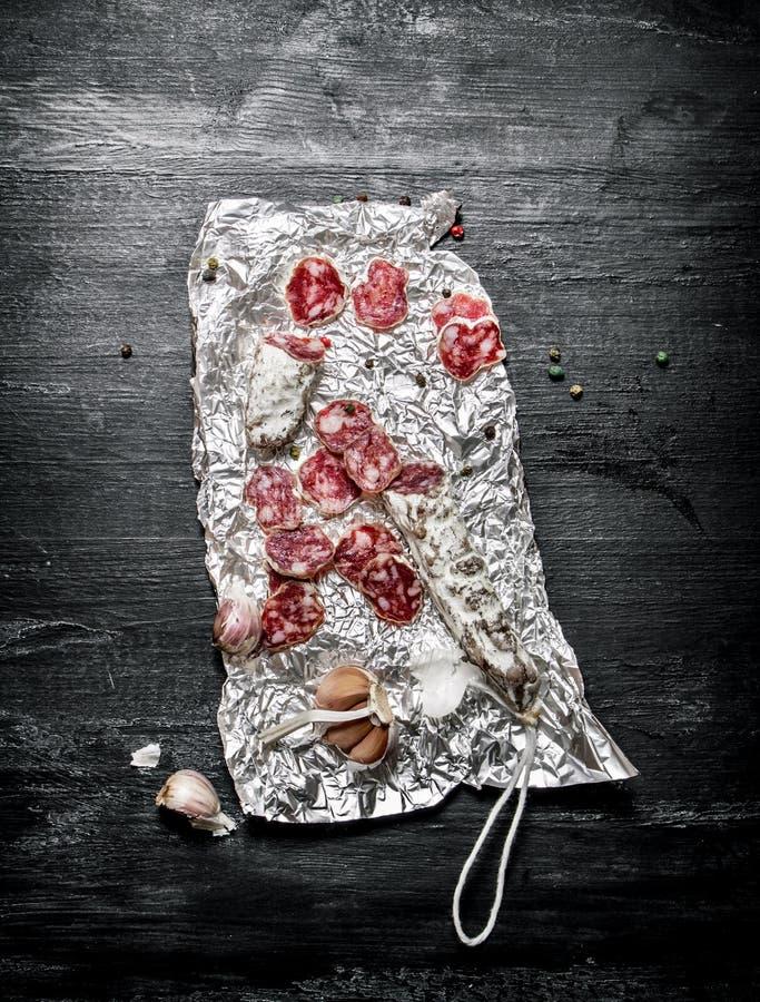 Kryddig salami med kryddor på folien royaltyfri bild