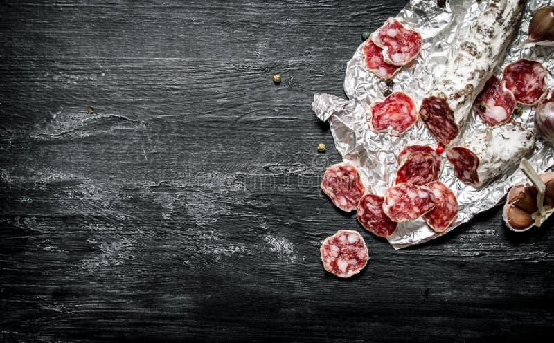 Kryddig salami med kryddor på folien arkivbilder