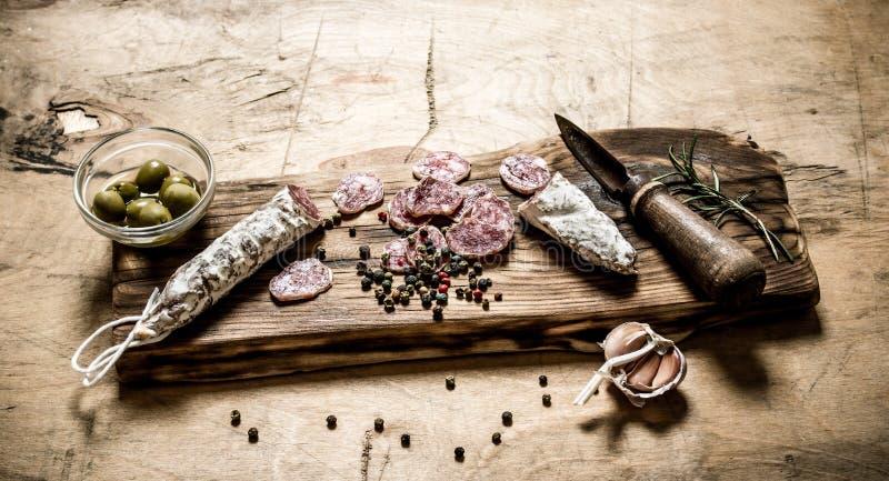 Kryddig salami med kryddor, rosmarin och oliv på brädet royaltyfri foto