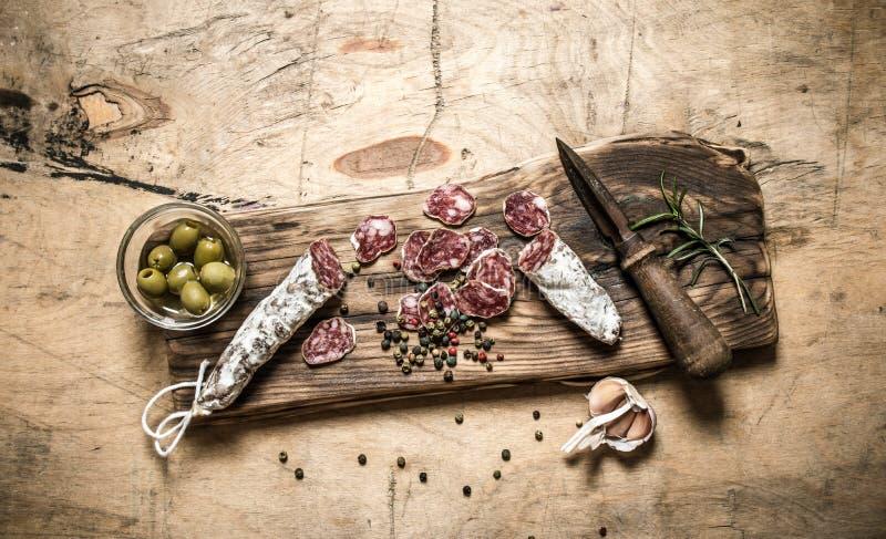 Kryddig salami med kryddor, rosmarin och oliv på brädet arkivfoto