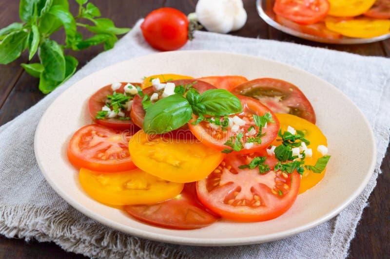 Kryddig sallad av guling, röda svarta tomater, snittet in i cirklar med vitlök och gräsplaner royaltyfri bild