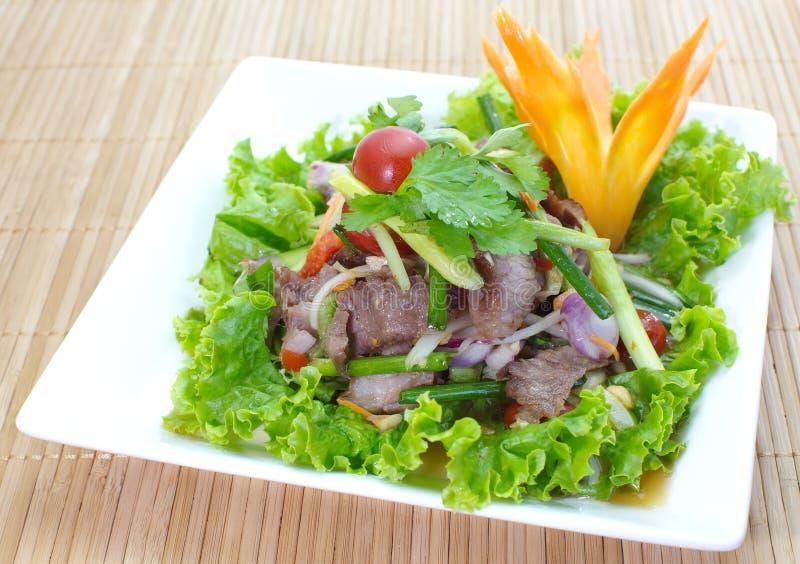 Kryddig sallad med griskött och gräsplanörten royaltyfria foton