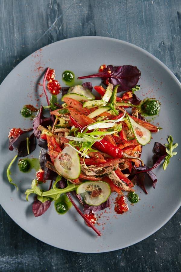 Kryddig sallad med nötkött, gräsplaner, peppar, sesam, vitlök, chili och fotografering för bildbyråer