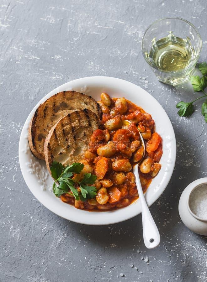 Kryddiga bräserade lima bönor i tomatsås och ciabattarostat bröd på en grå bakgrund Läckert vegetariskt lunchgrönsakprotein royaltyfri fotografi