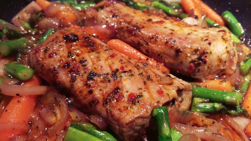 Kryddiga grisköttfransyskor som lagar mat med många grönsaker arkivbilder