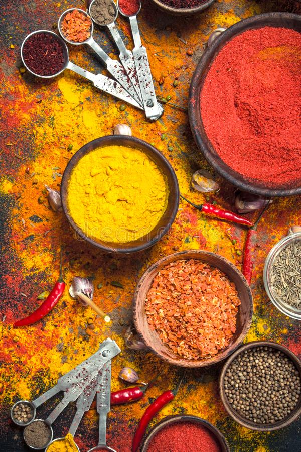 Kryddiga kryddor i bunkar med att mäta skedar arkivfoton