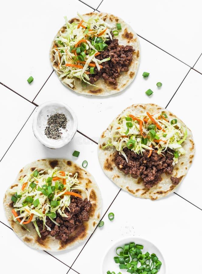 Kryddiga nötkött- och kålsalladtaco på ljus bakgrund, bästa sikt arkivbild