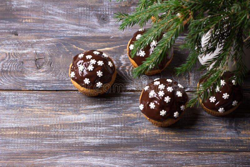 Kryddiga pumpamuffin med muttrar som dekoreras med chokladglasyr- och sockersnöflingor under julgranen på en trätabell royaltyfri fotografi