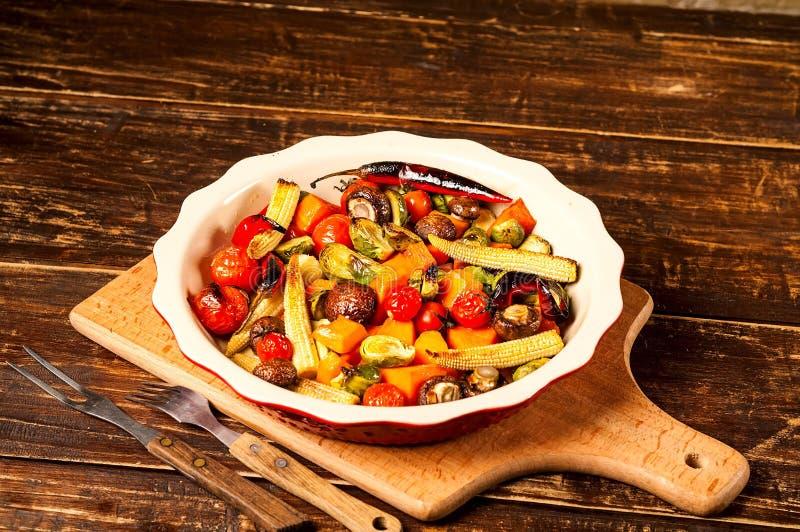 Kryddiga varma grönsaker som lagas mat på ett galler i keramisk bunke på trä royaltyfri foto