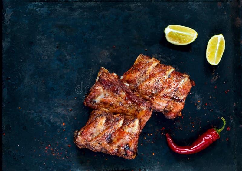 Kryddiga varma grillade extra- stöd från BBQ tjänade som med peppar och limefrukt för varm chili på mörk bakgrund baner Bästa sik arkivfoto