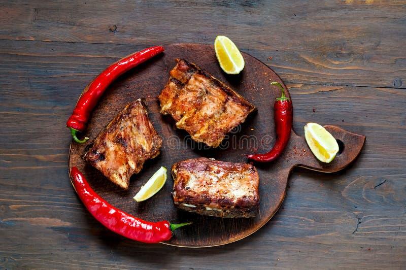 Kryddiga varma grillade extra- stöd från BBQ tjänade som med peppar och limefrukt för varm chili på mörk träbakgrund baner Top be fotografering för bildbyråer