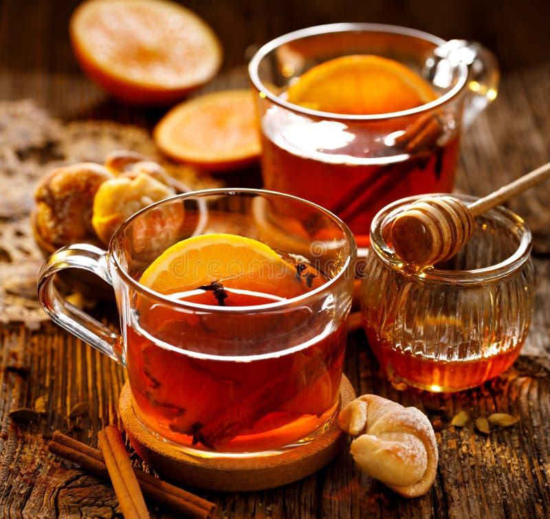 Kryddigt citrust varmt te med ingefära-, kryddnejlika-, kanel- och apelsinskivor, läckert som värme och som är sunda i glass kopp royaltyfri foto