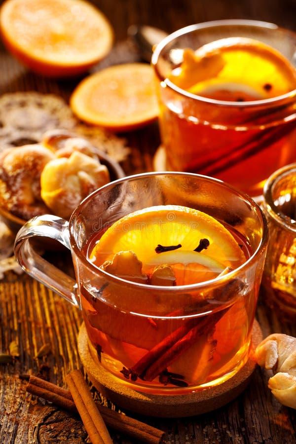 Kryddigt citrust varmt te med ingefära-, kryddnejlika-, kanel- och apelsinskivor, läckert som värme och som är sunda i glass kopp arkivfoto