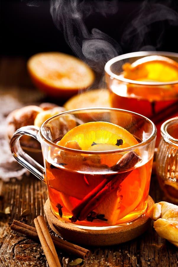 Kryddigt citrust varmt te med ingefära-, kryddnejlika-, kanel- och apelsinskivor, läckert som värme och som är sunda i glass kopp royaltyfria foton