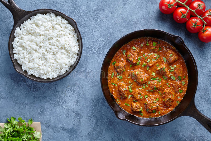 Kryddigt Madras smörnötkött saktar kocklammmat med ris och tomater i gjutjärnpanna royaltyfria bilder