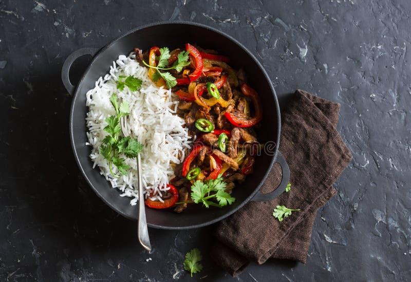 Kryddigt nötkött med grönsaker och ris i en gjutjärnkastrull på en mörk bakgrund, bästa sikt royaltyfria bilder