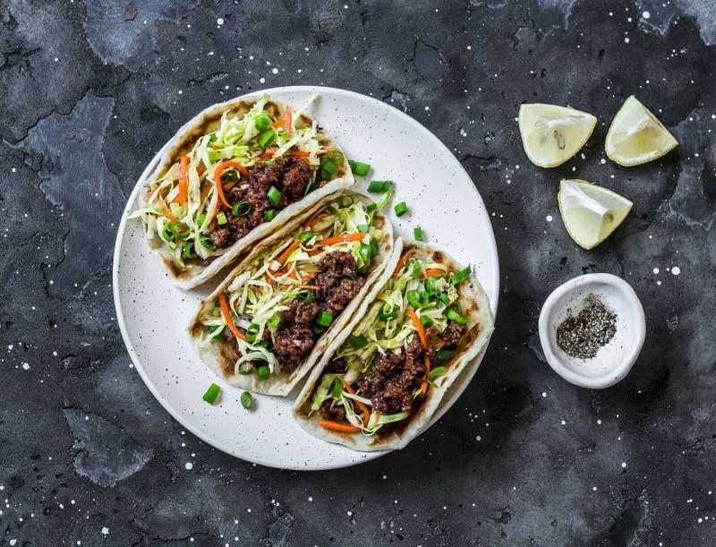 Kryddigt nötkött och kål, morötter gravade salladtaco på mörk bakgrund, bästa sikt royaltyfri fotografi