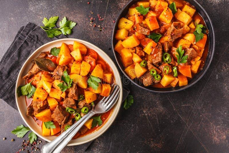 Kryddigt nötkött som låtas småkoka med potatisar i tomatsås, bästa sikt meat arkivbilder