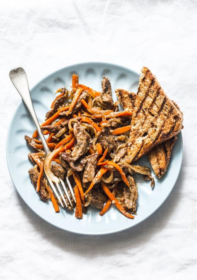 Kryddigt stekt nötkött wokar med morötter på en ljus bakgrund, bästa sikt arkivbild