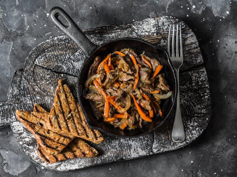 Kryddigt stekt nötkött wokar med sichuan peppar, morötter, lökar i stekpannan på en mörk bakgrund, bästa sikt arkivbild
