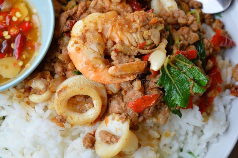 Kryddigt stekt under omrörning blandat skaldjur- och kotlettgriskött med basilika spricker ut på ris arkivfoto