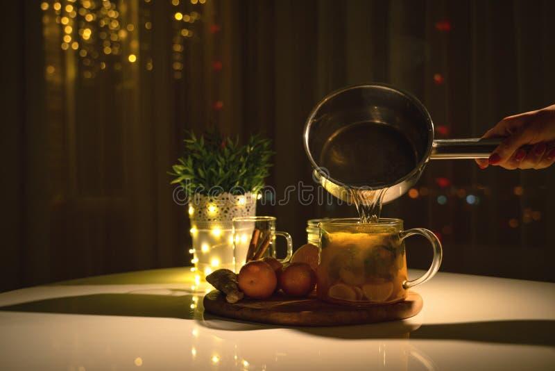 Kryddigt te i en kopp med kanel, honung, gurkmeja på en träbakgrund varm drink kopiera avstånd Defocused abstrakt julbakgrund arkivbild