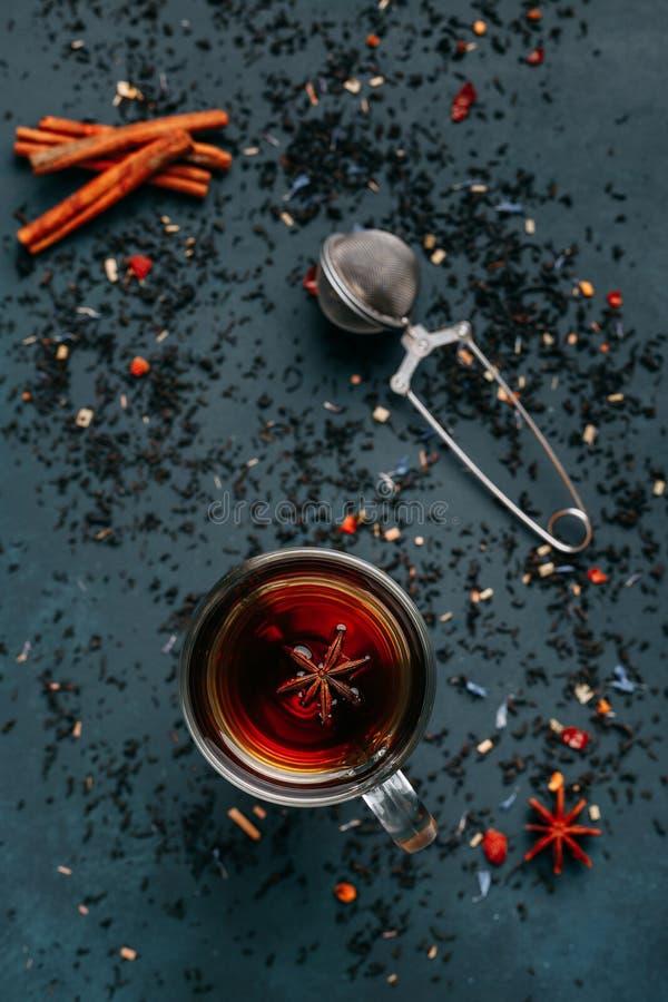 Kryddigt värmesvart te i en glass kopp med anis, kanel, te arkivbilder