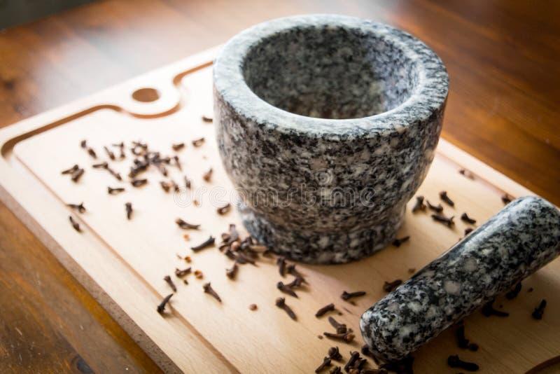 Kryddnejlika med mortelstöten och mortel arkivbilder