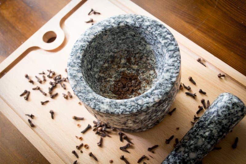 Kryddnejlika med mortelstöten och mortel fotografering för bildbyråer