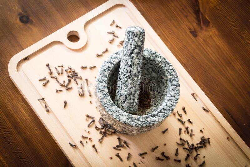 Kryddnejlika med mortelstöten och mortel royaltyfria foton