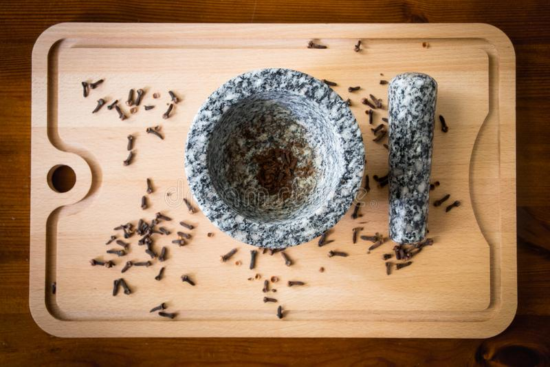 Kryddnejlika med mortelstöten och mortel royaltyfria bilder