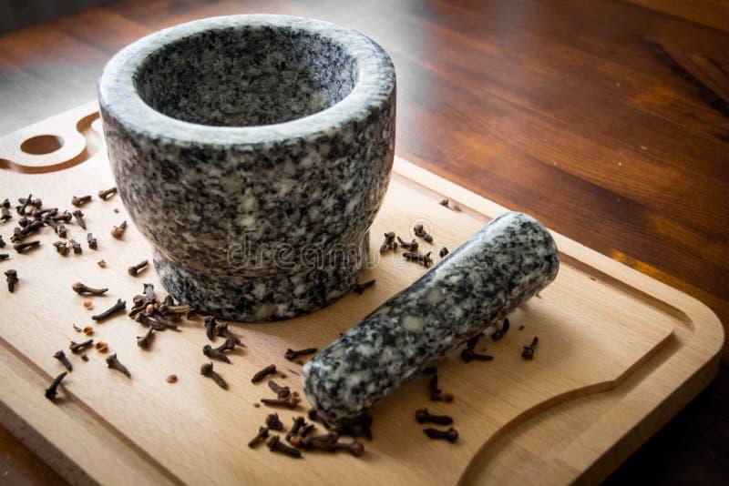 Kryddnejlika med mortelstöten och mortel arkivfoto