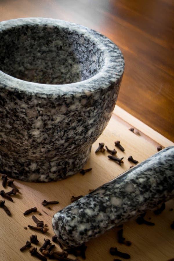 Kryddnejlika med mortelstöten och mortel royaltyfri fotografi