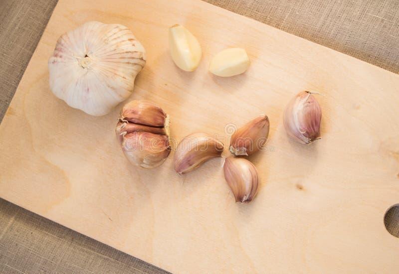 Kryddnejlikor och kryddnejlika av vitlök på träskärbräda royaltyfria foton
