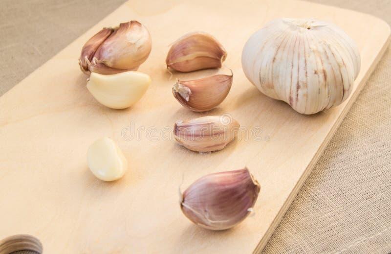 Kryddnejlikor och kryddnejlika av vitlök på träskärbräda arkivbild