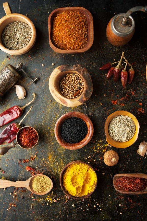 Kryddor, örter och smaktillsatser på en tabell i en sked arkivbilder