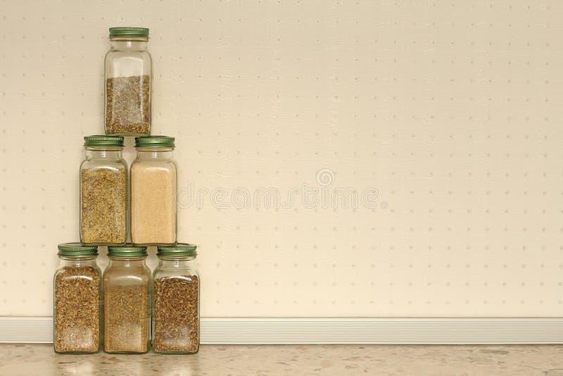 Kryddor i exponeringsglaskrus på en ljus bakgrund i köket Basilika oregano, italienska örter Pyramid av krus med kryddor kopiera  arkivbild