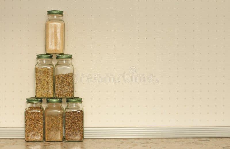 Kryddor i exponeringsglaskrus på en ljus bakgrund i köket Basilika oregano, italienska örter Pyramid av krus med kryddor kopiera  royaltyfri foto