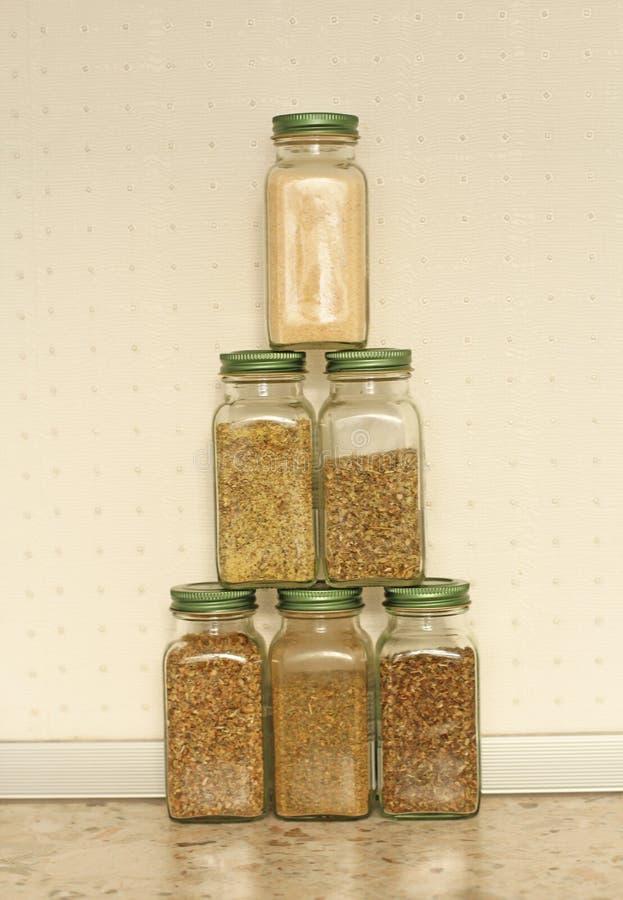 Kryddor i exponeringsglaskrus på en ljus bakgrund i köket Basilika oregano, italienska örter Pyramid av krus med kryddor kopiera  royaltyfri fotografi