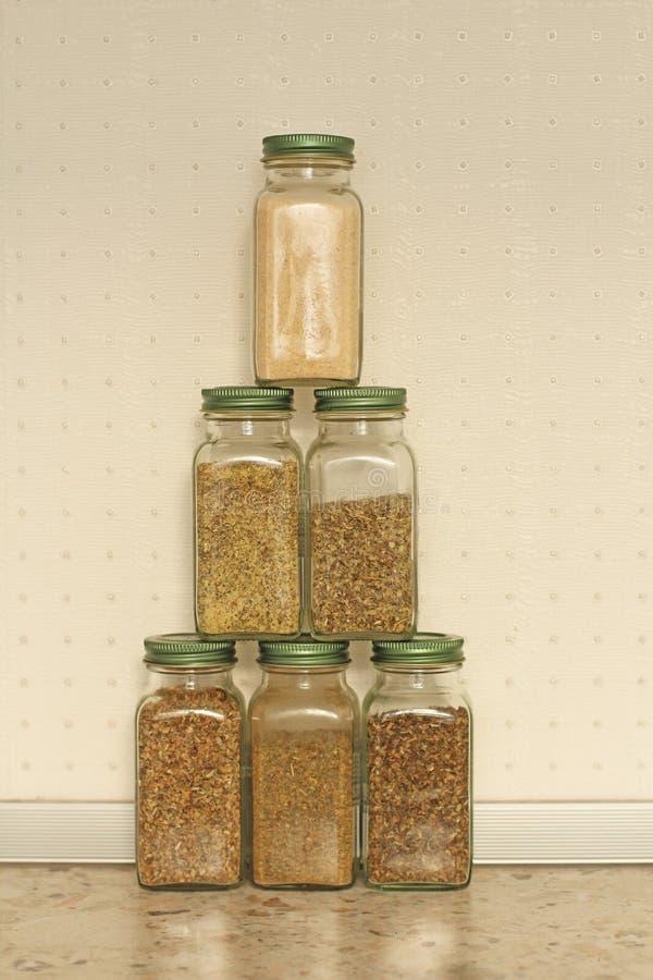 Kryddor i exponeringsglaskrus p? en ljus bakgrund i k?ket Basilika oregano, italienska ?rter Pyramid av krus med kryddor kopiera  royaltyfria bilder