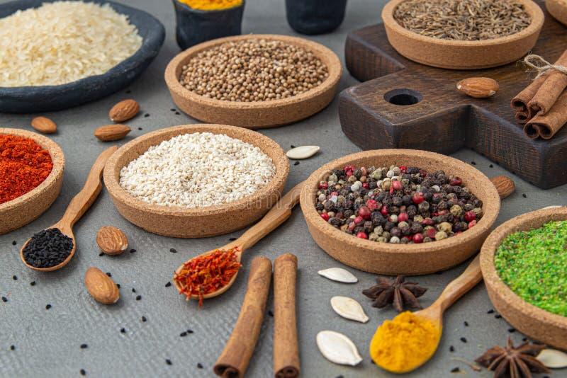 Kryddor ligger i bunkar och träskedar på en grå bakgrund arkivfoton