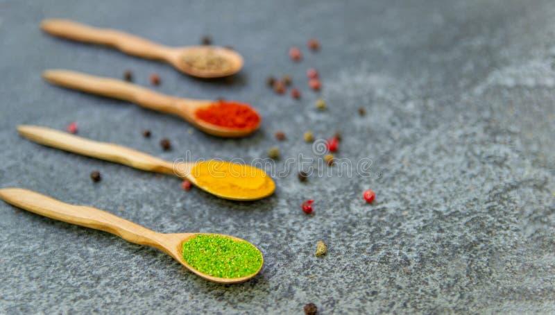 Kryddor ligger i träskedar på en svart bakgrund, den bästa sikten, mjuk fokus arkivbilder