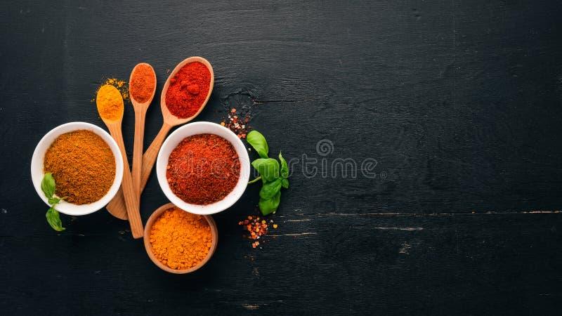 Kryddor och ?rter p? ett tr?br?de Peppra, salta, paprika, basilika, gurkmeja På en svart träsvart tavla royaltyfria foton
