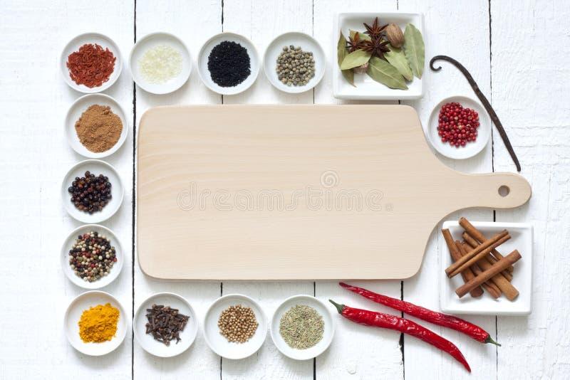 Kryddor och torkade grönsaker med skärbrädan royaltyfri fotografi