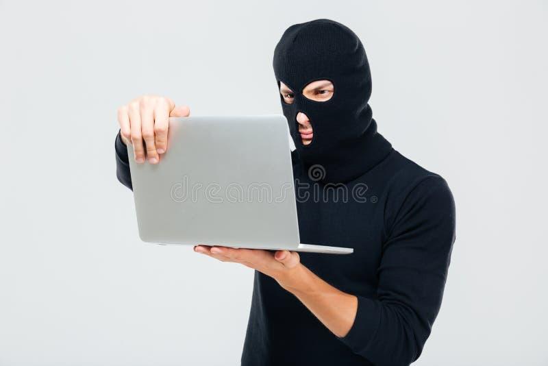 Kryminalny młody człowiek w balaclava pozyci i używać laptopie obraz stock