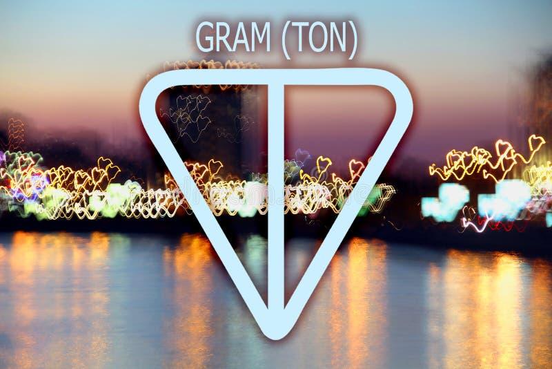 Kryptocurrency-logotyp i ton gram mot en suddig bakgrund av staden och floden med ljusslingor arkivfoto