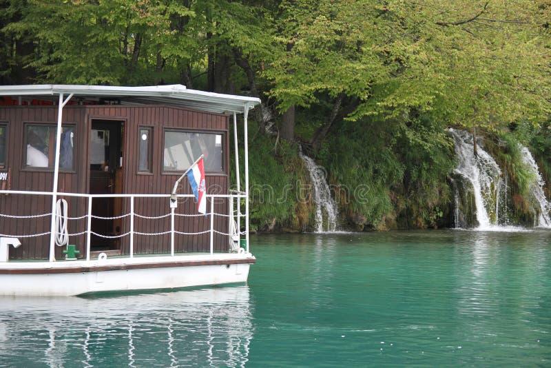 Kryssningskepp med en vattenfall i bakgrunden i Plitvice sjönationalparken royaltyfri foto